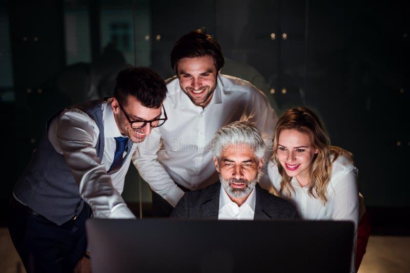 Un grupo de hombres de negocios en una oficina en la noche, usando el ordenador imágenes de archivo libres de regalías