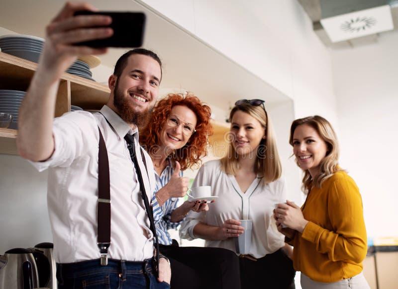 Un grupo de hombres de negocios jovenes con smartphone en el trabajo, tomando el selfie fotografía de archivo