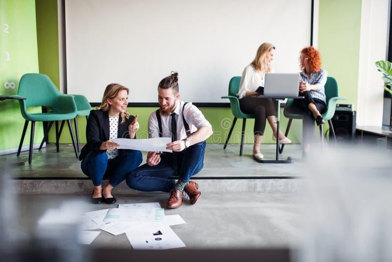 Un grupo de hombres de negocios jovenes que se sientan en el piso en una oficina, hablando foto de archivo libre de regalías