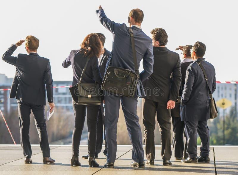 Un grupo de hombres de negocios se coloca en una plataforma mientras que uno señala en la distancia fotografía de archivo