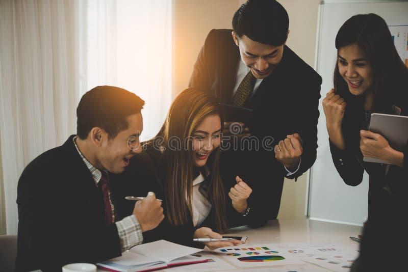 Un grupo de hombres de negocios y las mujeres encantan, alegre un mee del negocio fotos de archivo