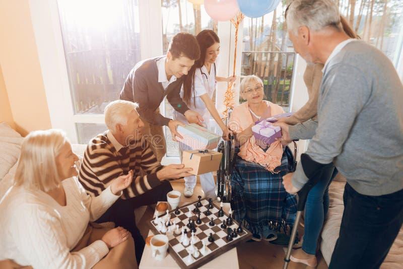 Un grupo de jóvenes y las personas mayores en una clínica de reposo felicitan a una mujer mayor en su cumpleaños foto de archivo libre de regalías