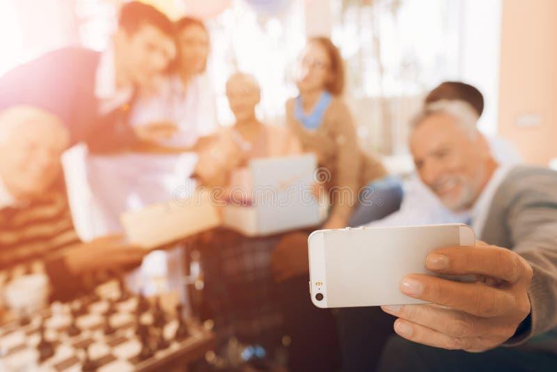 Un grupo de jóvenes y las personas mayores en una clínica de reposo hacen un selfie en un smartphone con una mujer mayor foto de archivo