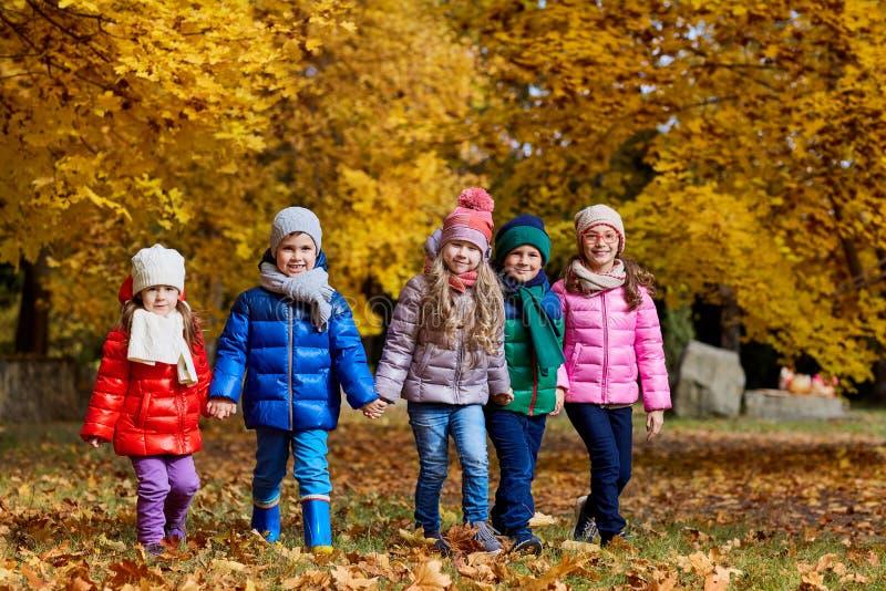 Un grupo de juego de niños en el otoño del amarillo del parque Niños pequeños imagenes de archivo