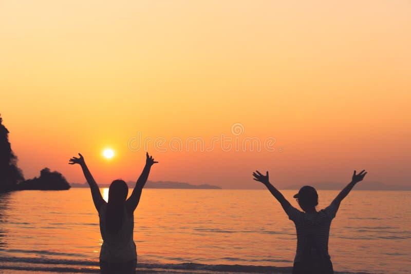 Un grupo de las manos de la subida de la mujer hasta concepto de la libertad del cielo con el fondo del cielo azul y de la playa fotos de archivo