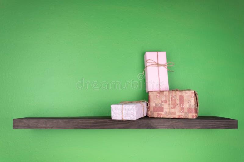 Un grupo de los regalos del Año Nuevo se llena en un estante del color oscuro que se fija en la pared del verde imágenes de archivo libres de regalías