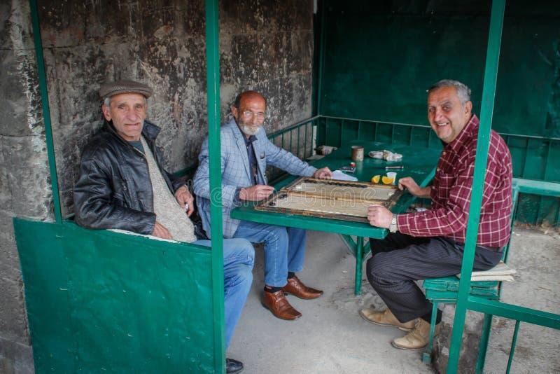 Un grupo de más viejos hombres se está relajando jugando a backgammon foto de archivo libre de regalías