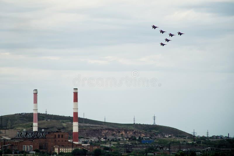 Un grupo de 6 moscas rusas del MiG 29 del fulcro-UNo del combatiente sobre la empresa industrial de la ciudad fotos de archivo