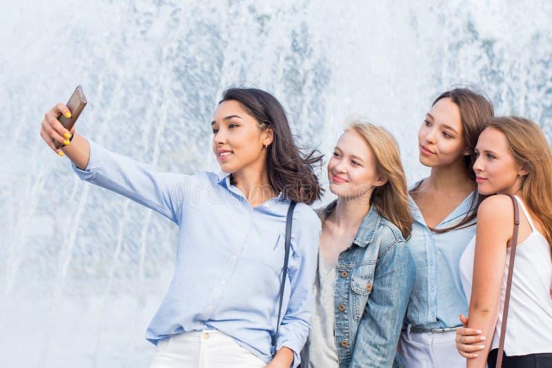 Un grupo de muchachas atractivas jovenes de estudiantes hace un selfie en el fondo de una fuente hermosa imágenes de archivo libres de regalías