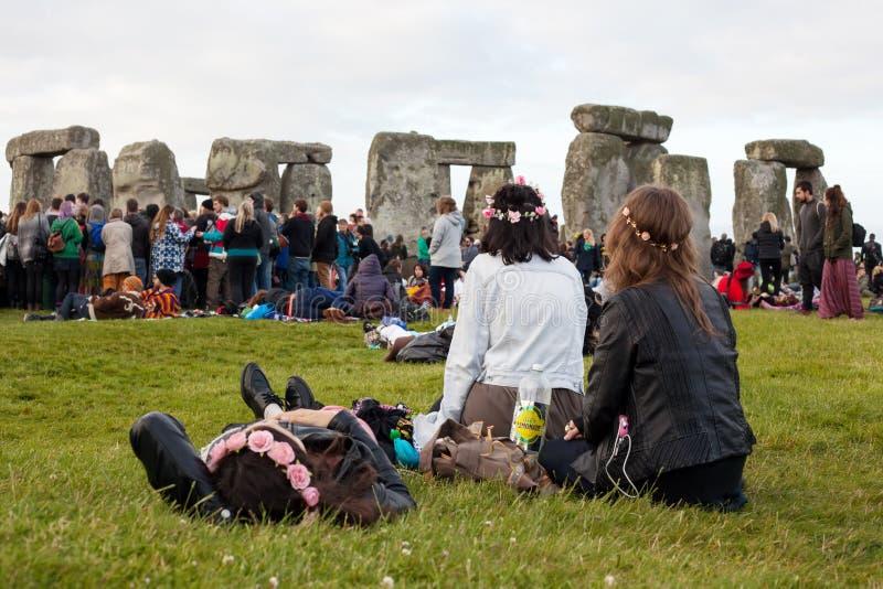 Un grupo de muchachas con las flores en sus juerguistas del reloj del pelo en el solsticio de verano de Stonehenge imagenes de archivo