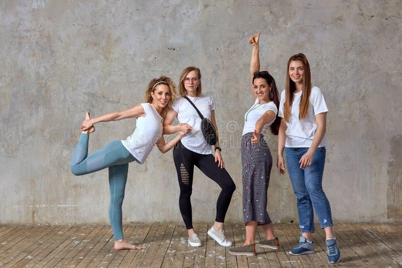 Un grupo de muchachas hermosas que presentan para la cámara contra la pared Trabajo en equipo del concepto, amistad, encontrando  foto de archivo libre de regalías