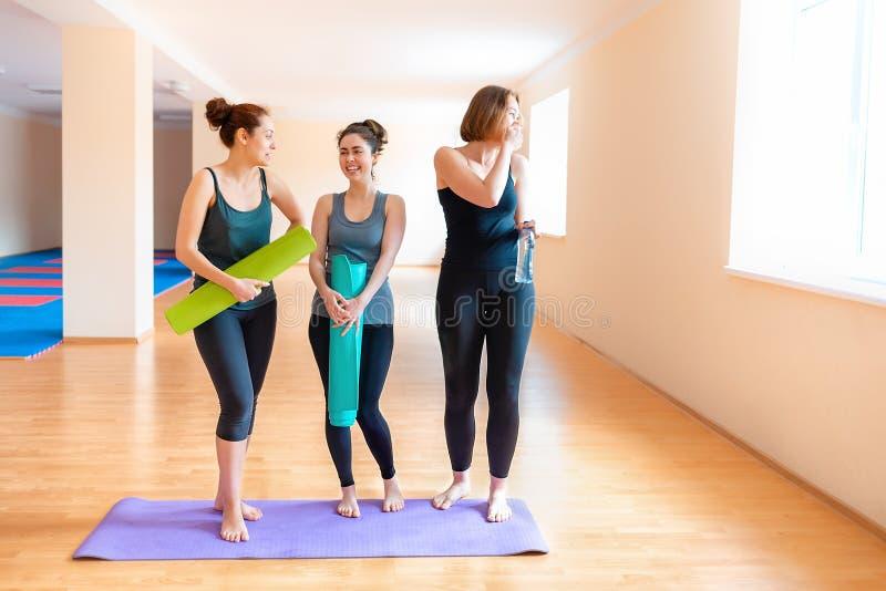 Un grupo de mujeres jovenes con las esteras en sus manos que charlan antes de entrenar El concepto de forma de vida, de gimnasia  fotos de archivo libres de regalías