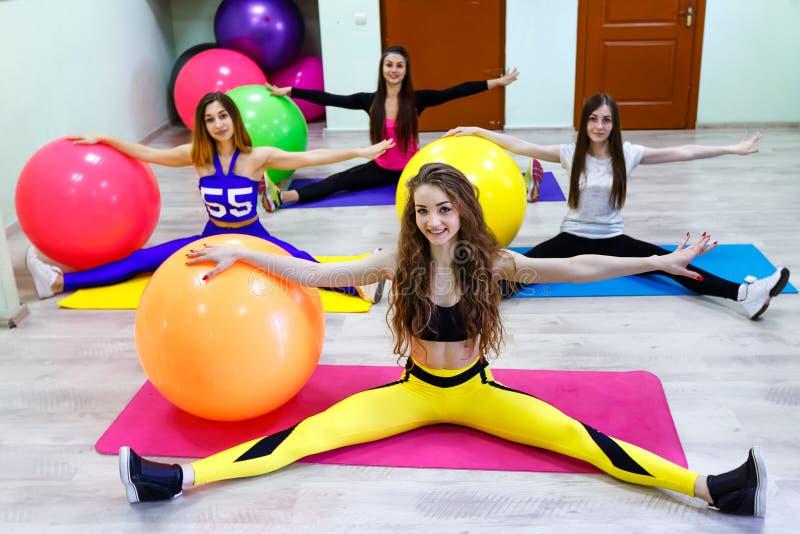 Un grupo de mujeres jovenes que hacen ejercicios con las bolas del ajuste en un fitne imagenes de archivo