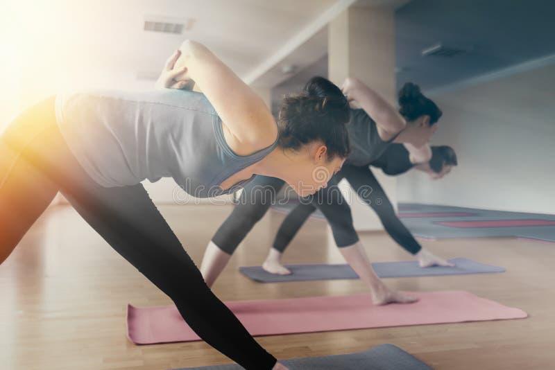Un grupo de mujeres jovenes que hacen yoga en la sala de clase El concepto de forma de vida de los deportes, de salud y de equili foto de archivo libre de regalías