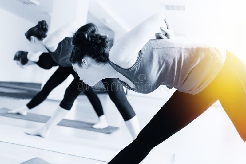 Un grupo de mujeres jovenes que hacen yoga en la sala de clase El concepto de forma de vida de los deportes, de salud y de equili fotografía de archivo libre de regalías