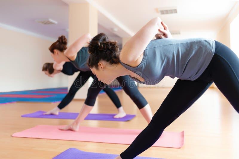 Un grupo de mujeres jovenes que hacen yoga en la sala de clase El concepto de forma de vida de los deportes, de salud y de equili fotos de archivo