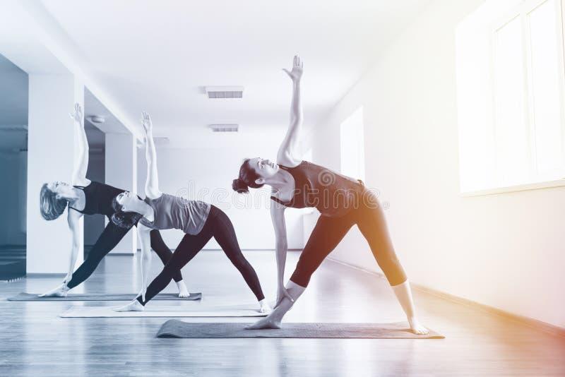Un grupo de mujeres jovenes que hacen yoga en la sala de clase El concepto de forma de vida de los deportes, de salud y de prácti imágenes de archivo libres de regalías