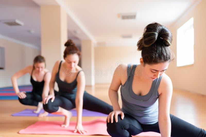Un grupo de mujeres jovenes que hacen yoga en la sala de clase El concepto de práctica de los deportes, de los aeróbicos y de la  imagenes de archivo