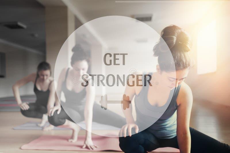 Un grupo de mujeres jovenes que hacen yoga en la sala de clase El concepto de práctica de los deportes, de los aeróbicos y de la  fotografía de archivo libre de regalías