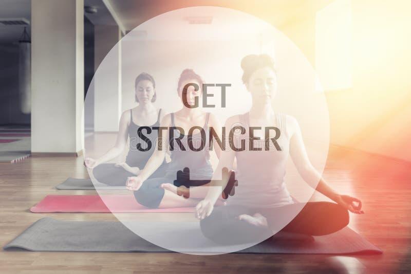 Un grupo de mujeres jovenes que hacen yoga en la sala de clase El concepto de práctica de los deportes, de la meditación y de la  foto de archivo