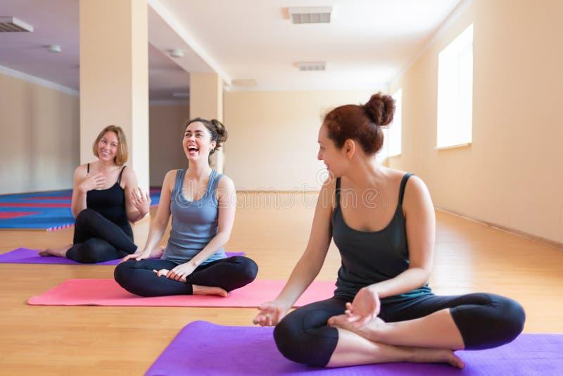 Un grupo de mujeres jovenes se divierte que charlan con uno a después de un entrenamiento El concepto de deporte, de yoga y de so imagenes de archivo