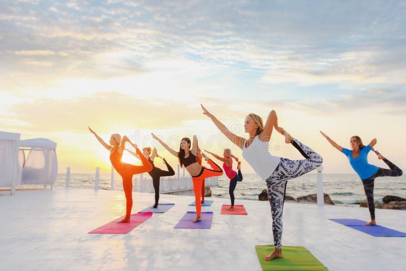 Un grupo de mujeres que hacen yoga en la salida del sol cerca del mar imagenes de archivo