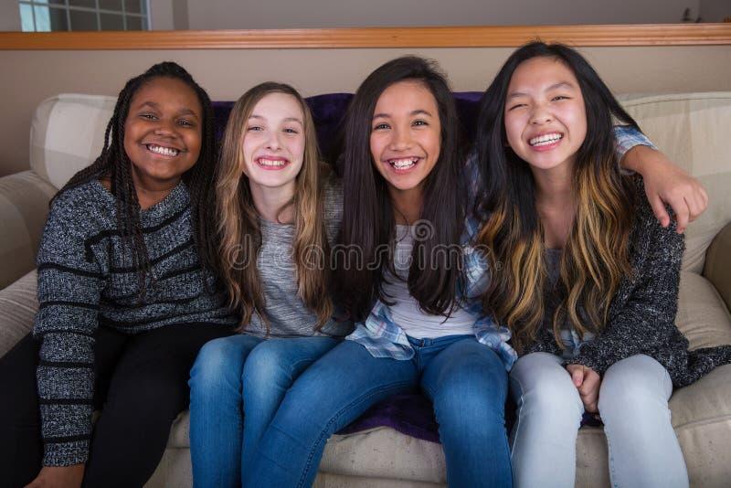 Un grupo de niños felices que se sientan en un sofá en casa foto de archivo