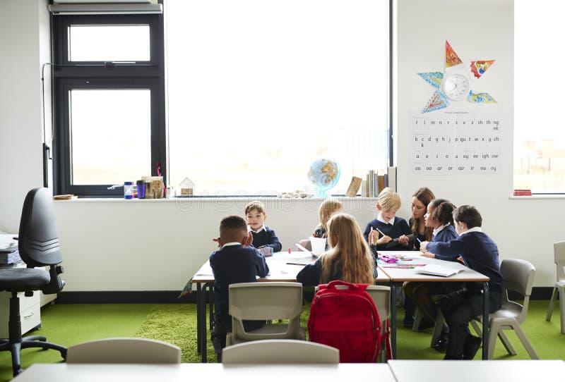 Un grupo de niños de la escuela primaria que se sientan en la tabla en una sala de clase, profesor que se arrodilla para ayudarle fotografía de archivo libre de regalías
