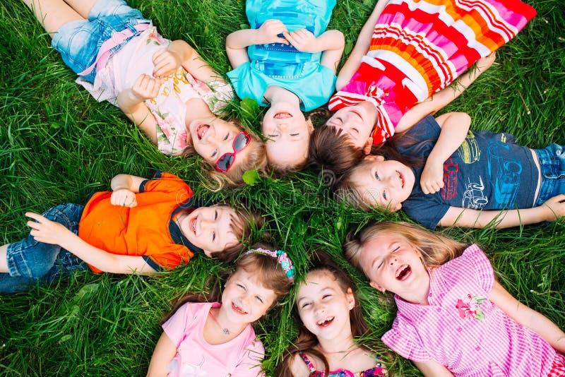 Un grupo de niños que mienten en la hierba verde en el parque La interacción de los niños fotos de archivo libres de regalías