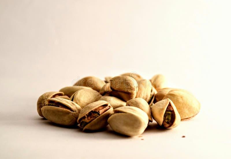 Un grupo de nueces de pistacho en el fondo blanco imágenes de archivo libres de regalías