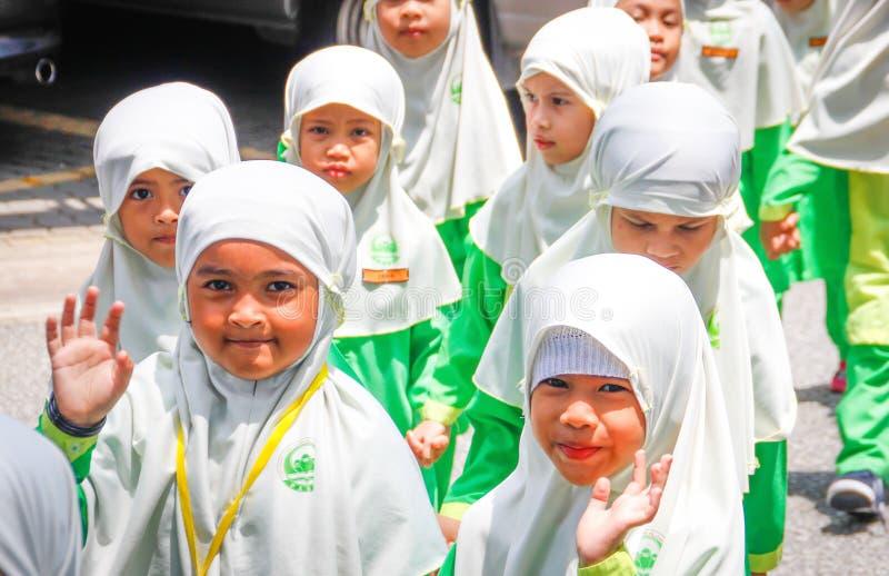 Un grupo de pequeñas muchachas asiáticas de la escuela primaria en los hijabs blancos imagenes de archivo