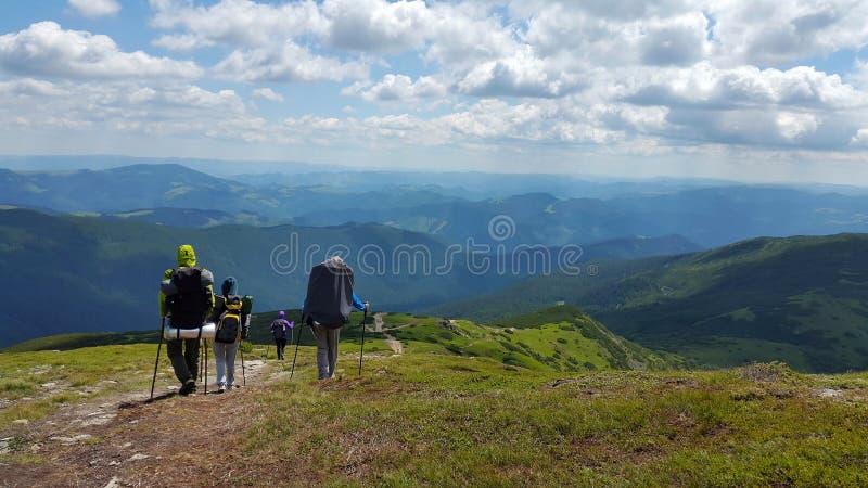 Un grupo de personas con las mochilas va en las montañas con paisaje hermoso imagen de archivo libre de regalías