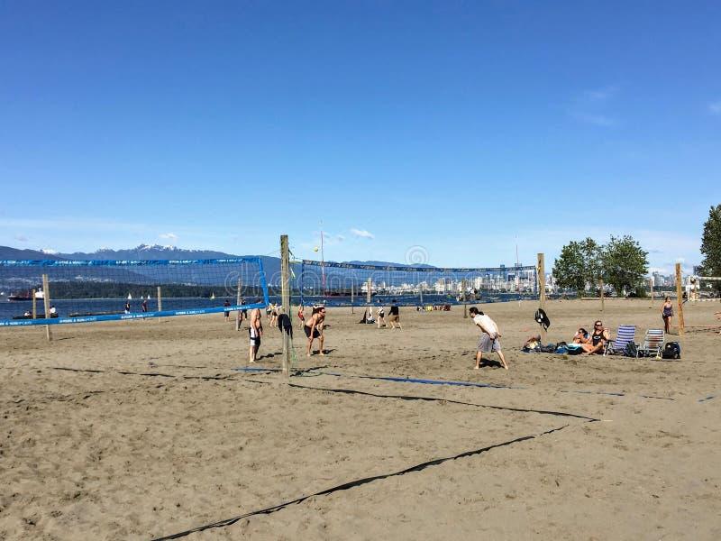 Un grupo de personas que juega a voleibol de playa en un d?a soleado hermoso a lo largo de las playas arenosas de los bancos espa imagenes de archivo