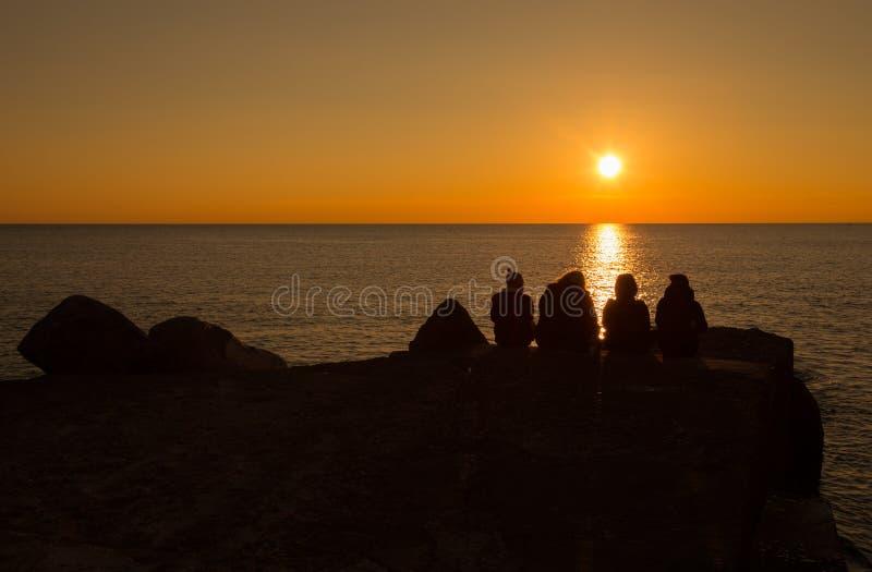 Un grupo de personas se sienta abajo mirando puesta del sol delante del mar imagen de archivo