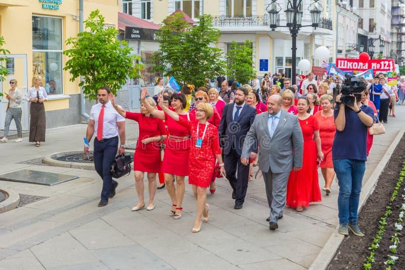 Un grupo de profesores en una columna durante la procesión festiva de los diplomados de escuela secundaria foto de archivo
