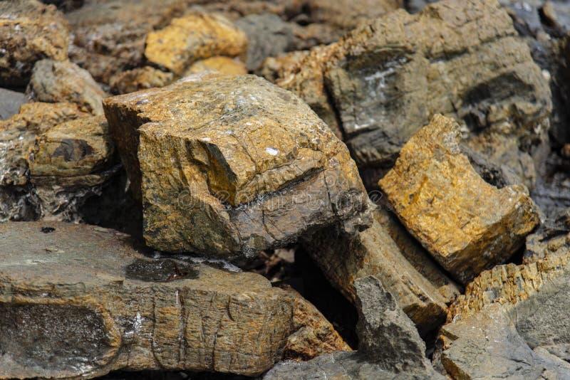 Un grupo de rocas en la arena como fondo imagen de archivo libre de regalías