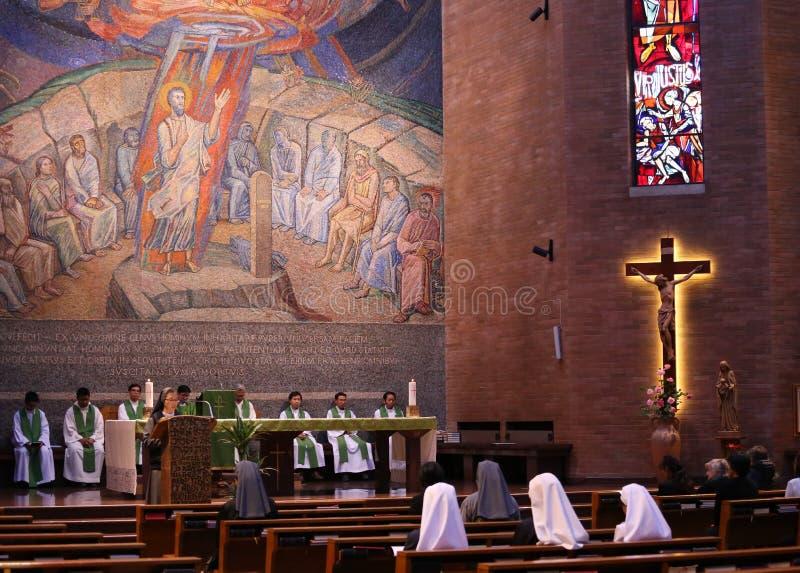 Un grupo de sacerdote católico y de hermanas en la misa santa imagenes de archivo