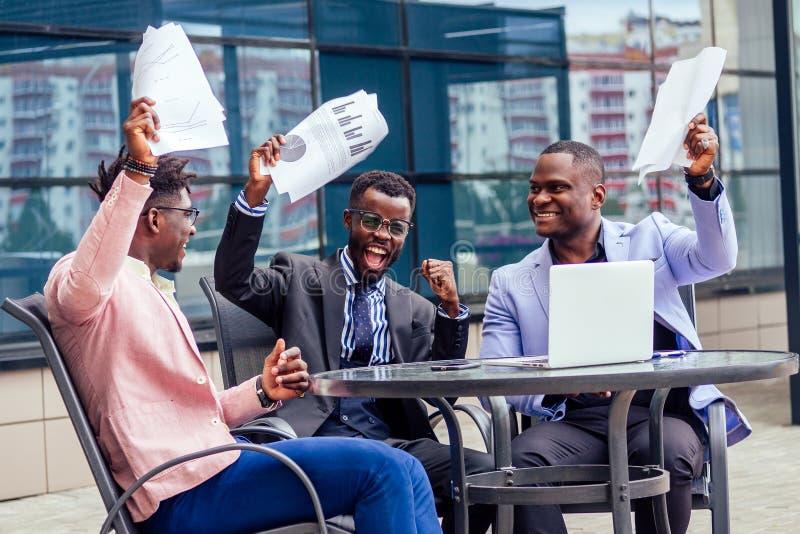 Un grupo de sus tres exitosos empresarios afroamericanos con un traje elegante se sienta a la mesa y trabaja con un portátil foto de archivo libre de regalías