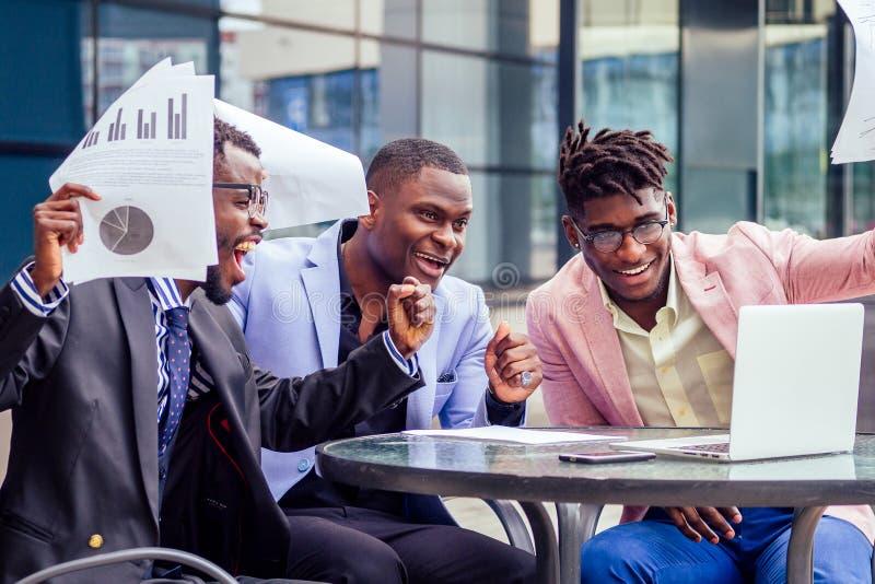 Un grupo de sus tres exitosos empresarios afroamericanos con un traje elegante se sienta a la mesa y trabaja con un portátil fotos de archivo
