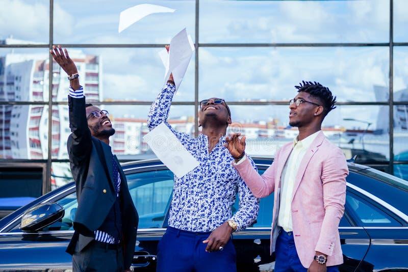 Un grupo de sus tres exitosos y guapos hombres de negocios afroamericanos con un traje elegante arroja papeles contra un fotos de archivo libres de regalías