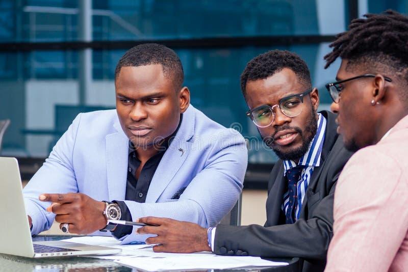 Un grupo de tres estilosos empresarios afroamericanos en traje de negocios de moda trabajando en mesa con imágenes de archivo libres de regalías