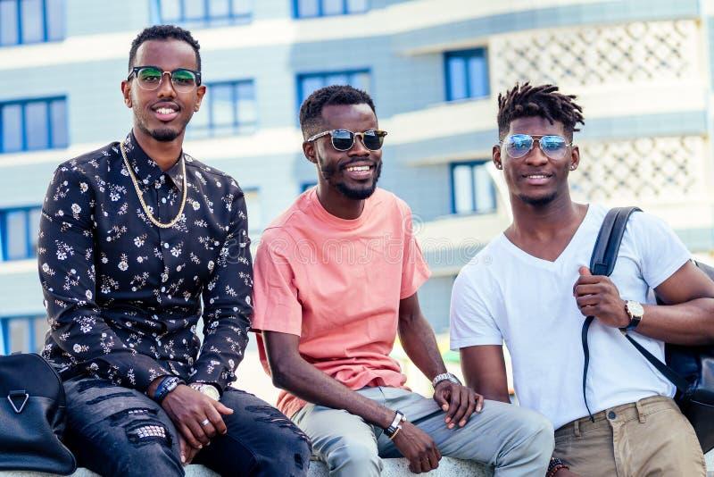 Un grupo de tres estudiantes afroamericanos de moda que se comunican en la calle imágenes de archivo libres de regalías