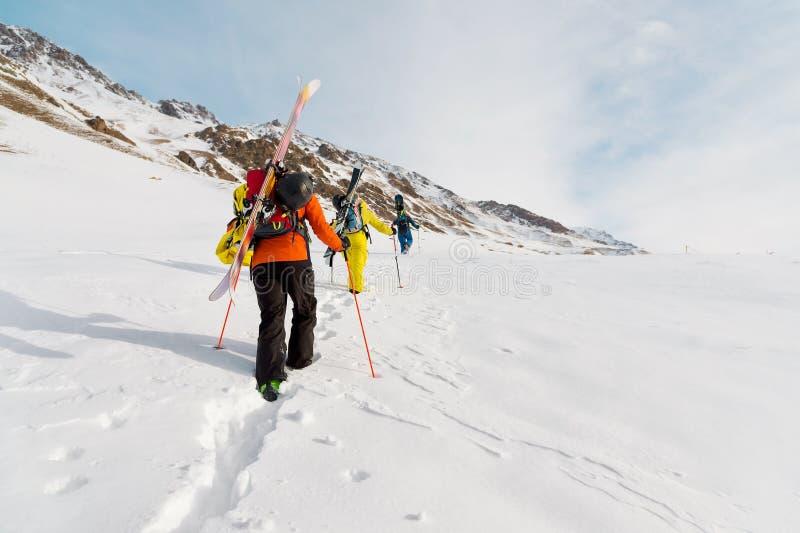 Un grupo de tres freeriders sube la montaña para el esquí backcountry a lo largo de las cuestas salvajes del fotos de archivo