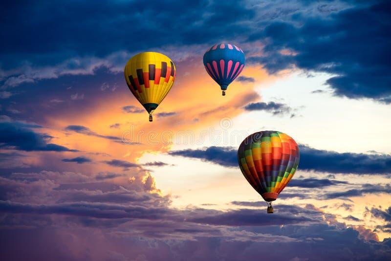 Un grupo de tres globos coloridos del aire caliente que ascienden en un cielo de la puesta del sol con las nubes dramáticas hermo fotografía de archivo