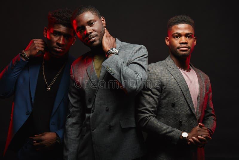 Un grupo de tres hombres africanos en la presentaci?n elegante de los trajes aislados en estudio fotos de archivo