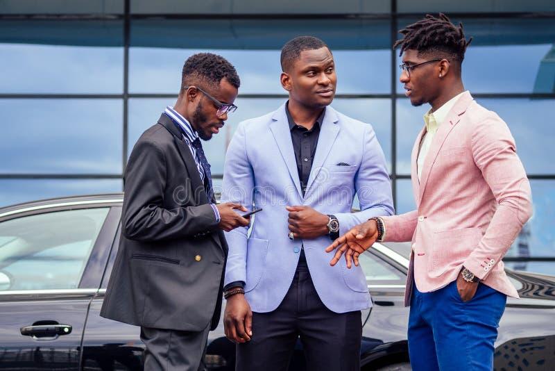 Un grupo de tres hombres de negocios afroamericanos con trajes elegantes comunican discusiones en la calle fotografía de archivo