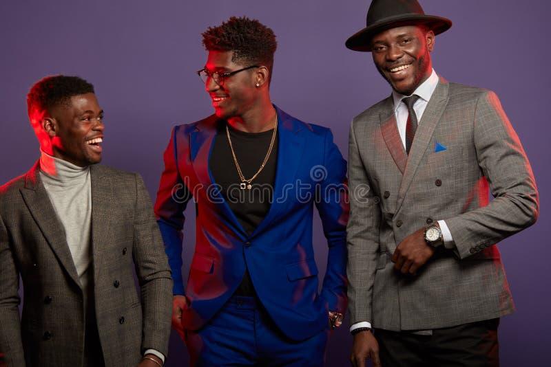 Un grupo de tres hombres negros en la presentaci?n elegante de los trajes aislados en estudio foto de archivo