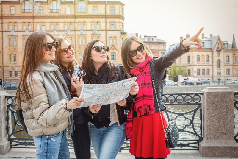 Un grupo de turistas femeninos jovenes está buscando atracciones en una ciudad europea en el mapa Cuatro alegres y hermosos imagen de archivo