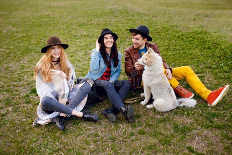 Un grupo de una gente joven, sonriente pasa tiempo así como su perro fornido, sentándose en hierba, fondo de la naturaleza imagenes de archivo