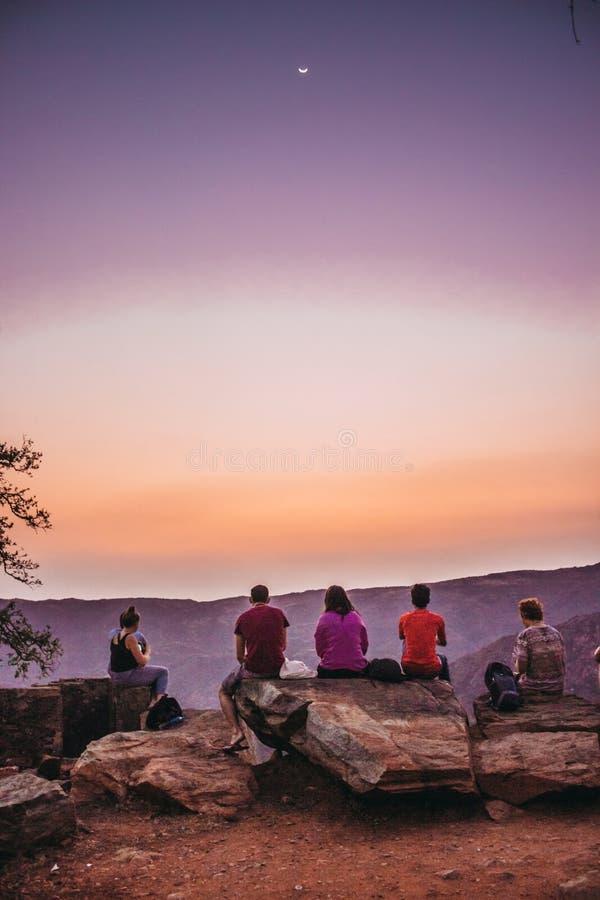 Un grupo de viajeros jovenes que se sientan encima de una montaña y que miran una hermosa vista del barranco imagen de archivo